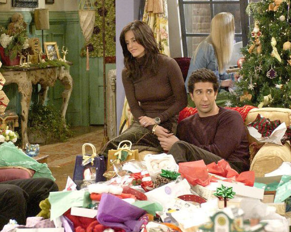 Festive scene with the Friends cast together in the girls apartment with tree and present unwrapping - Chandler is missing